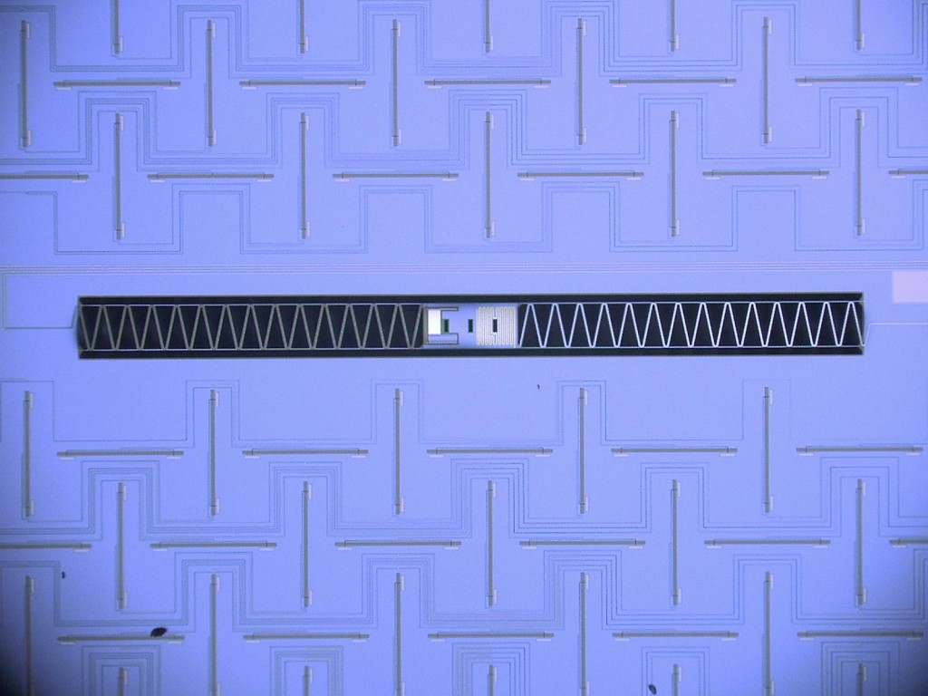 Photograph of a SPIDER detector island. The central island (0.3mm long) is suspended over a pit in the surrounding silicon wafer by thin legs.